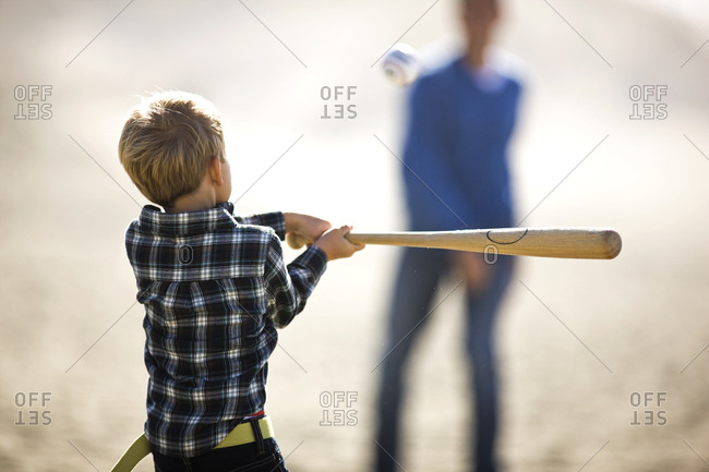 Young boy swinging a baseball bat at the beach.