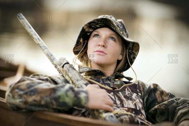 Young woman sitting in a boat holding a rifle