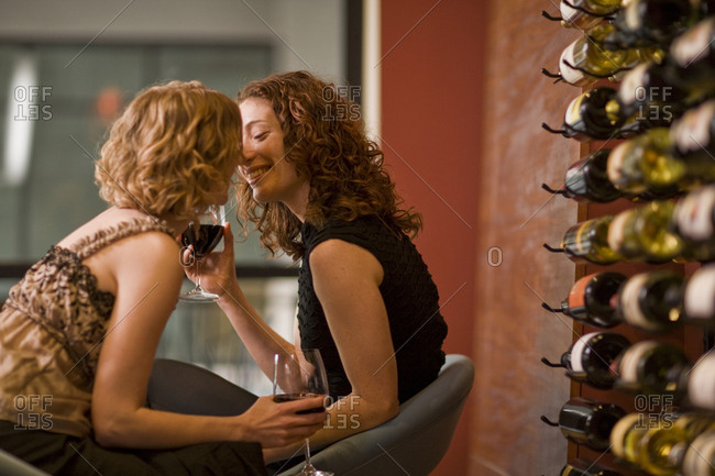 Lesbian couple drinking wine together and kissing