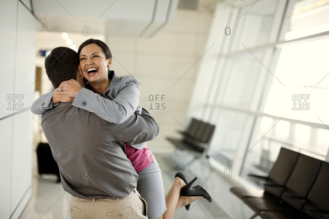 Mid adult woman grins happily as she joyfully hugs her husband who has met her at the airport arrivals gate.