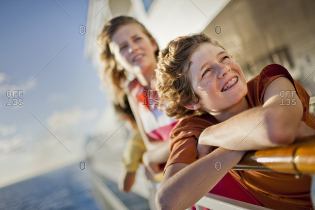Smiling teenaged siblings leaning over the railing of a moving boat.