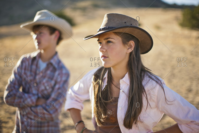Two unimpressed teenagers at a ranch.