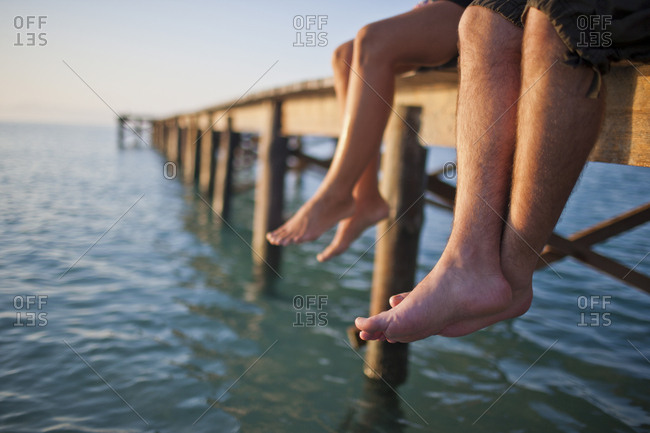 Two pairs of legs dangling off a wooden pier.