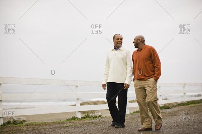 Men walking side by side along a beachside pavement