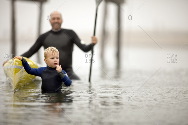 Young boy looks confused while standing next to a kayak with his father holding it steady as they stand in the waters of a foggy harbor.