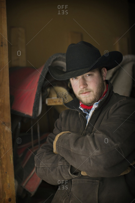 Portrait of young man in cowboy hat standing in doorway of tack shed