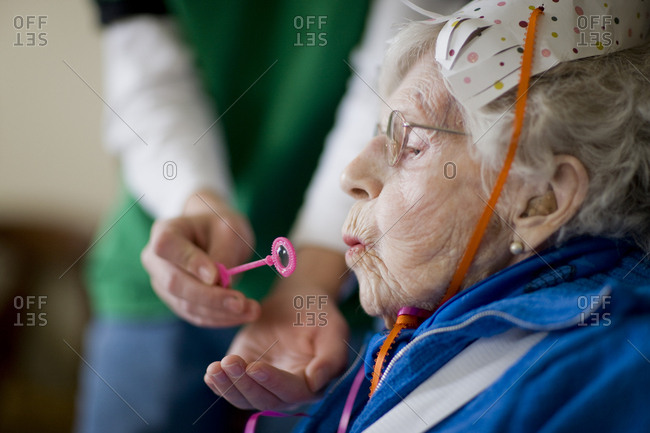 Boy helping great grandmother to blow bubbles