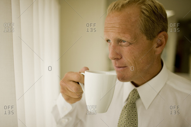 Businessman drinking coffee looking contemplative