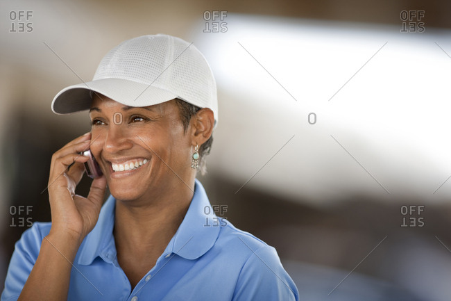 Woman in baseball cap and polo shirt on cellphone