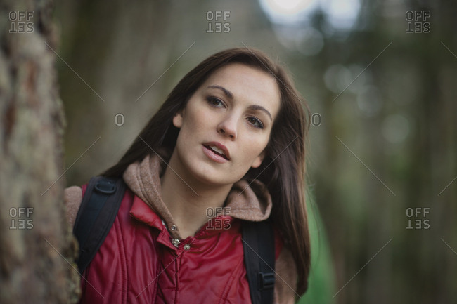 Portrait of brunette woman with backpack leaning on tree.