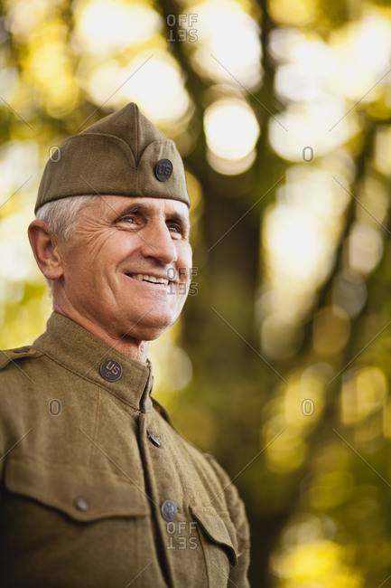 Mature male reenactor wearing an American World War II side cap and uniform looks away and smiles as he poses for a portrait.