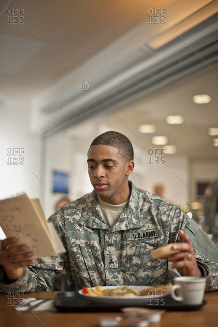 Young soldier forgets to eat his breakfast as he reads a letter from his young son at home.