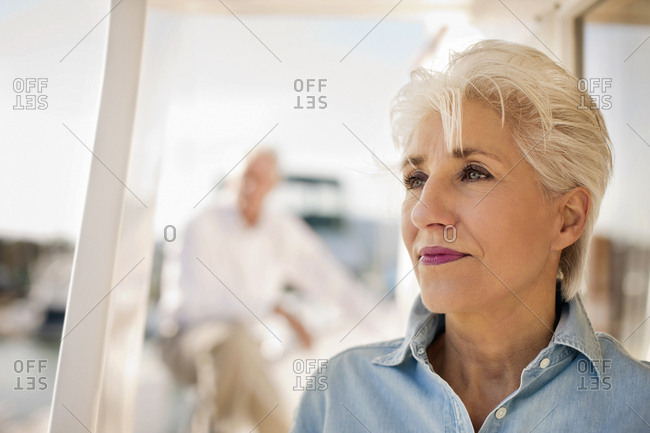 Senior woman looks out to sea while her husband stands in the background.