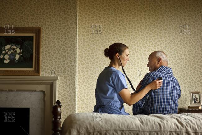 Nurse listening to elderly patient's heartbeat with stethoscope.