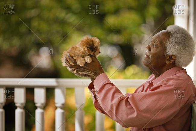 Man holding aloft a puppy.