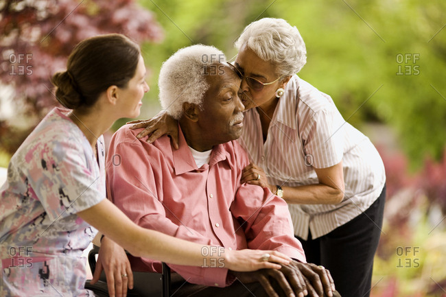 Nurse puts supportive hand on a senior man's knee as a senior woman leans down to hug him and kiss his forehead.