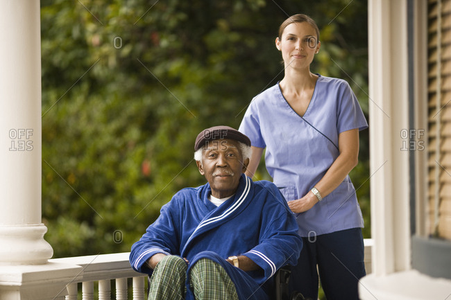 Senior man in a wheelchair and a female nurse pose for a portrait on a porch.