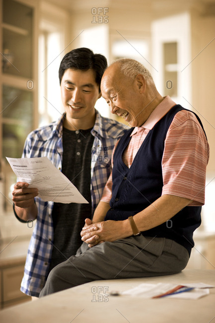 Young man shows a document to a smiling senior man sitting on a kitchen counter.