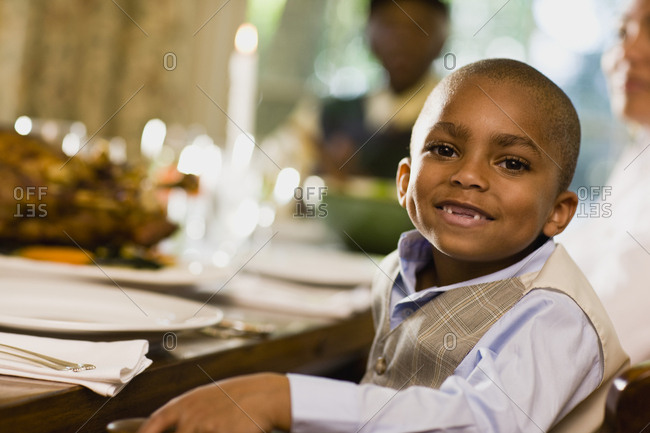 Young boy smiles as he poses for a portrait while sitting at a dining table set with a candle and food with a woman and a man in the background.