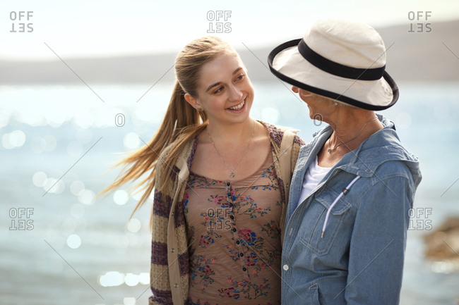 Smiling teenage girl standing on a beach with her grandmother.