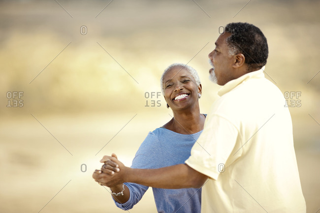 Smiling senior couple playfully dancing on a beach.