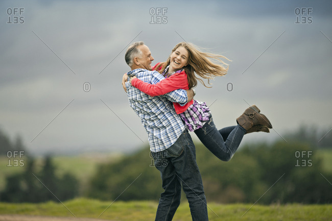 Happy middle aged man spinning his teenage daughter around.