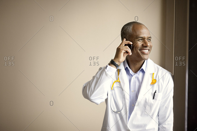 Excited mature doctor talking on cell phone.