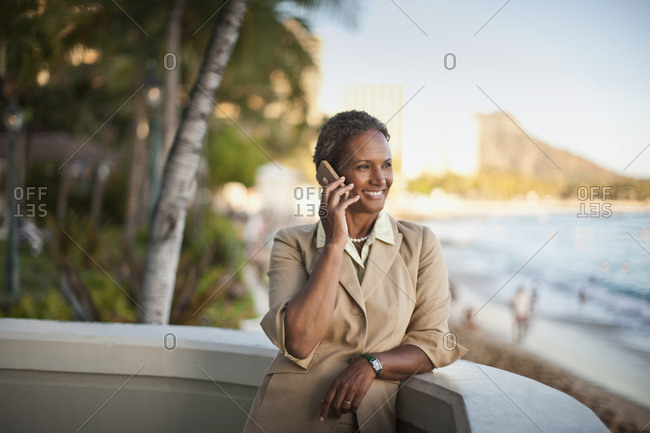 Businesswoman standing on hotel balcony, talking on cell phone.