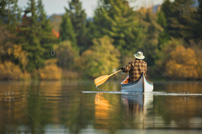 Man canoeing across a tranquil scenic lake.