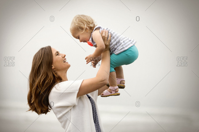 Smiling mother holding her baby daughter in the air.