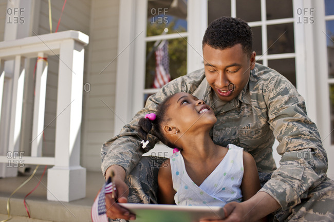 Smiling young girl looking at a digital tablet with her father on the front porch.