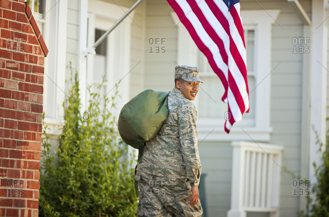 Portrait of a smiling young army soldier carrying a duffel bag outside his home.
