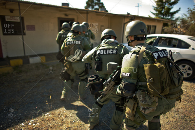 Group of police officers about to enter a building during an exercise at a training facility.