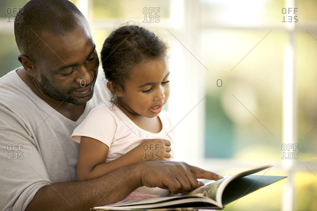 Young girl sitting on her father's lap while reading a book.