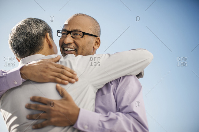 Businessmen greeting each other with a hug.