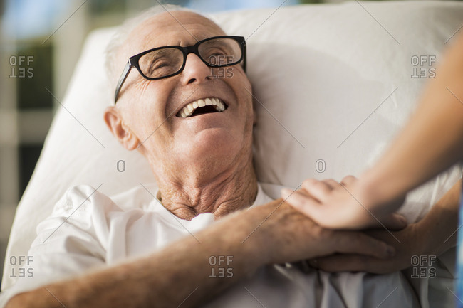 Elderly man in a rest home is cheered up by the gentle touch of a nurse.