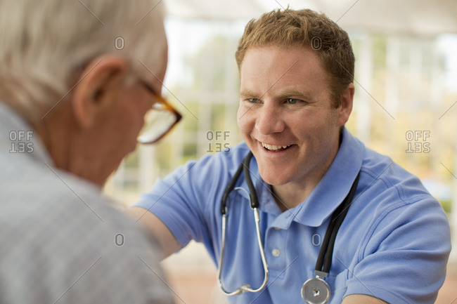 Smiling male nurse encouraging his elderly male patient as he talks with him.