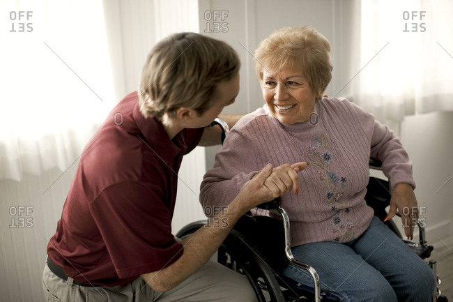 Smiling senior woman talking with a male nurse and being comforted while sitting in a wheelchair.