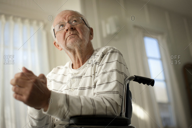 Hopeful senior man looking upward while sitting in a wheel chair with his hands clasped.