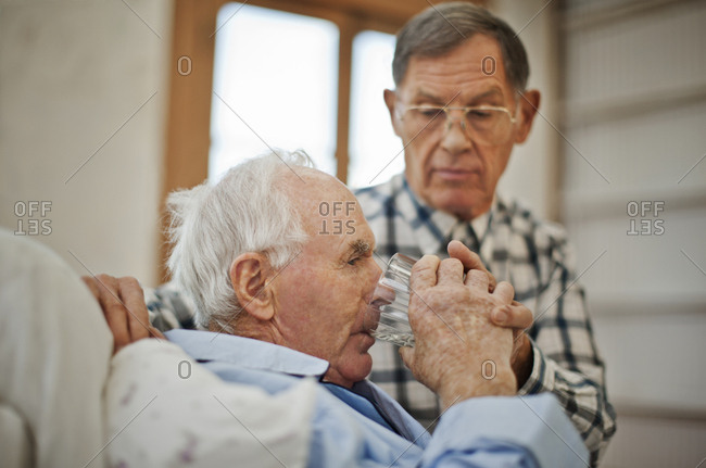 Ailing senior man drinking a glass of water in bed with the help of his concerned male friend.