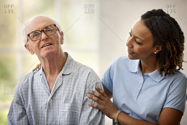 Female nurse listening to an elderly male patient while resting her hand on his shoulder.