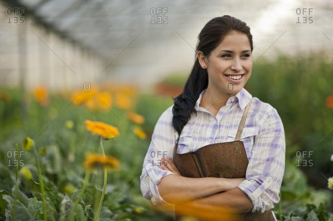 Teenage girl working in a greenhouse.