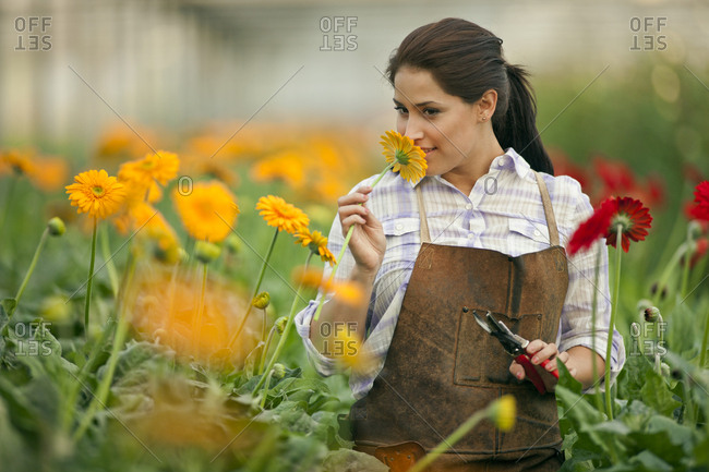 Teenage girl smelling a flower growing in a greenhouse.