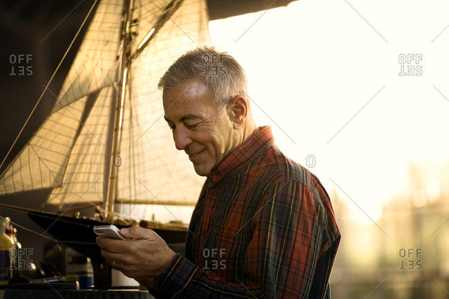Smiling senior man sending a text message on a cell phone.
