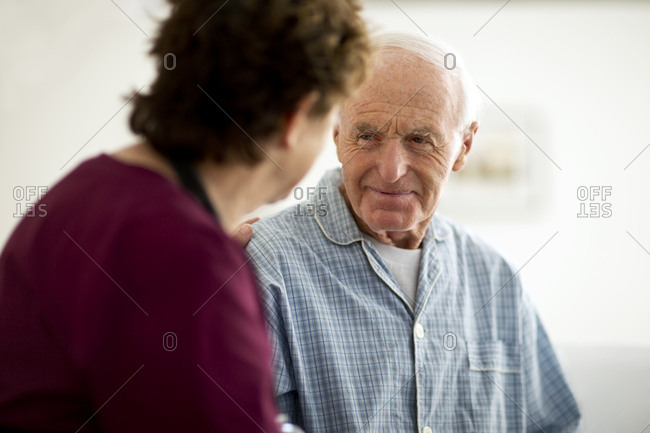 Thoughtful senior man listening to his nurse.