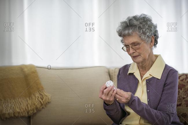 Concerned senior woman reading the label on a bottle of medication.