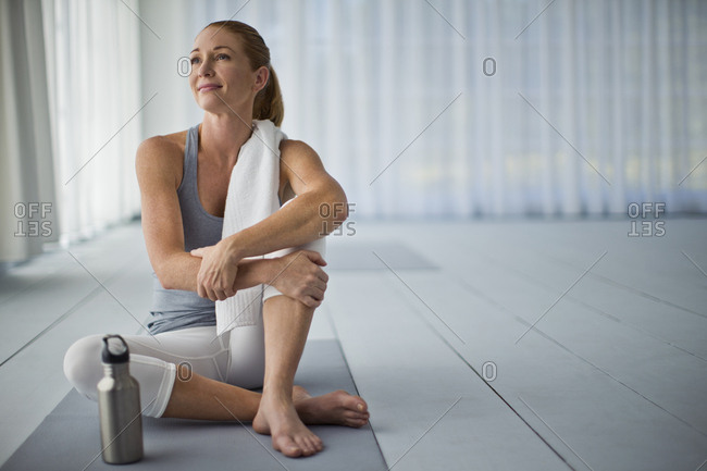 Thoughtful mid adult woman relaxing after a yoga class.