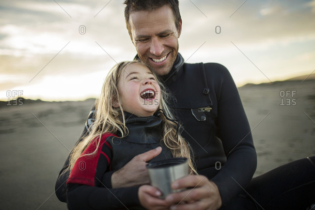 Smiling young girl and her father share a hot drink and laugh together as they relax on the beach after a long day.