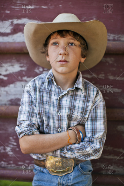Portrait of a serious young boy dressed as a rancher.