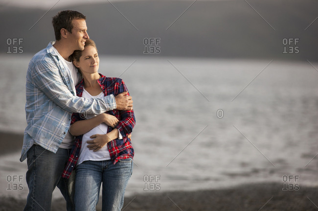 Middle-aged man gently embraces his pregnant wife on the beach.